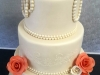 Ivory themed wedding cake with touch of coral